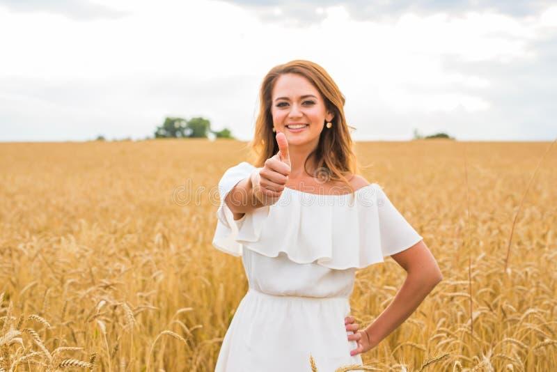 Bella giovane donna vi che dà i pollici su e che sorride in un campo con cielo blu fotografia stock libera da diritti
