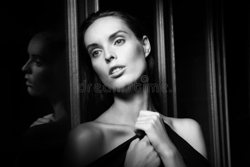 Bella giovane donna vicino ad un vetro nell'interno immagine stock