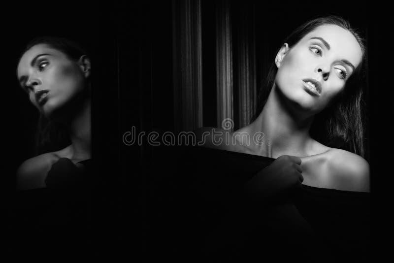 Bella giovane donna vicino ad un vetro nell'interno fotografia stock libera da diritti