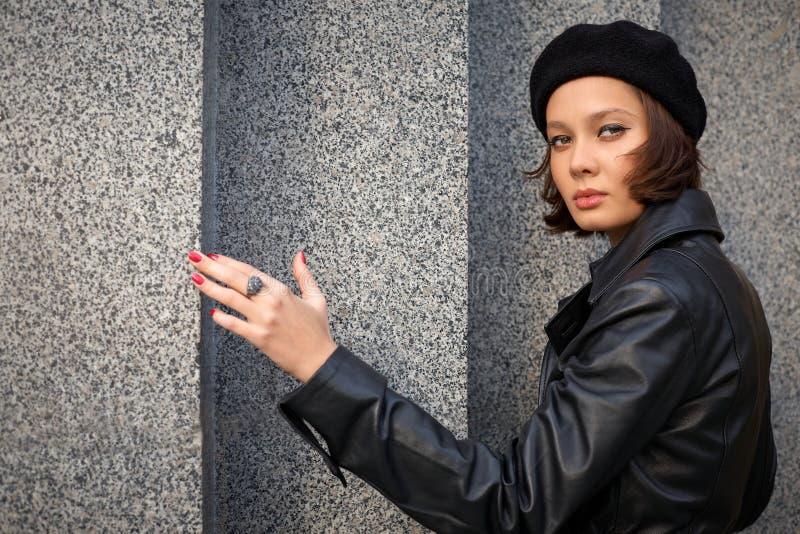 Bella giovane donna vicino alla parete fotografie stock libere da diritti
