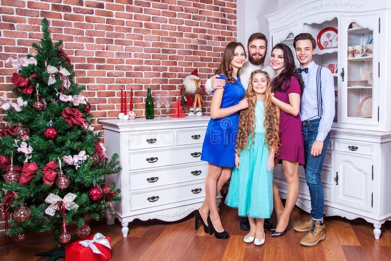 Bella giovane famiglia che gode del tempo di natale e che abbraccia con l'amore immagine stock