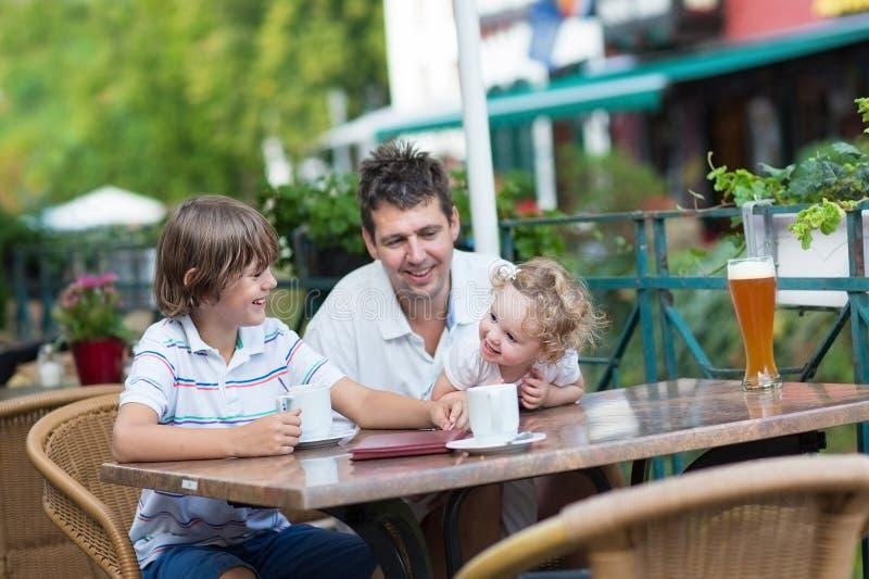 Bella giovane famiglia in un caffè esterno fotografia stock libera da diritti