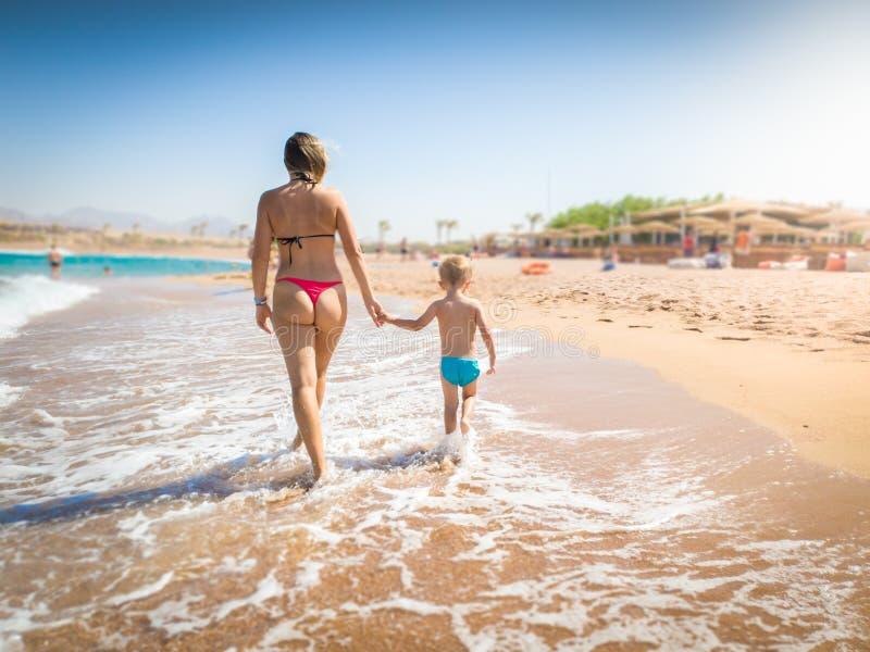 Bella giovane madre che tiene a mano il suo piccolo figlio e che cammina sulla spiaggia sabbiosa del mare al giorno soleggiato lu immagini stock