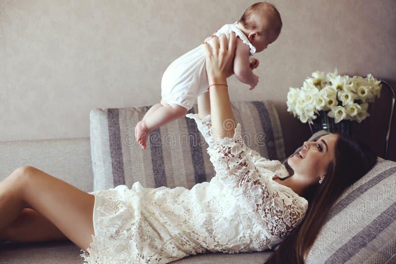 Bella giovane madre con capelli scuri lunghi che posano con il suo piccolo bambino adorabile immagine stock libera da diritti