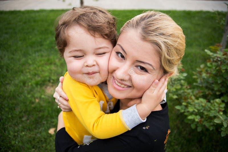 Bella giovane madre con un piccolo figlio sveglio sono felici, abbracciare, mostrante il loro amore puro fotografia stock libera da diritti