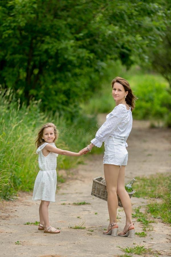 Bella giovane madre e la sua piccola figlia in vestito bianco divertendosi in un picnic Stanno su una strada nel parco, tenente immagine stock libera da diritti