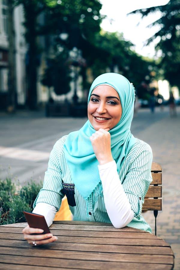 Bella giovane ragazza araba nel hijab che parla dal telefono al caffè fotografia stock libera da diritti