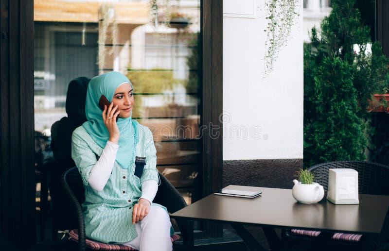 Bella giovane ragazza araba nel hijab che parla dal telefono al caffè immagini stock