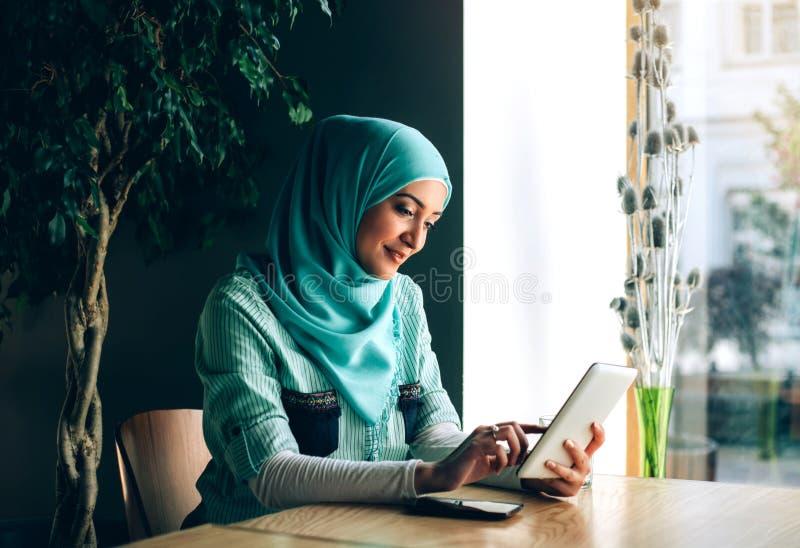 Bella giovane ragazza araba nel hijab che posa per la macchina fotografica al caffè immagini stock libere da diritti