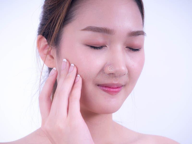 Bella giovane ragazza asiatica con il tocco fresco pulito della pelle il propri fronte, cosmetologia, bellezza e stazione termale fotografia stock
