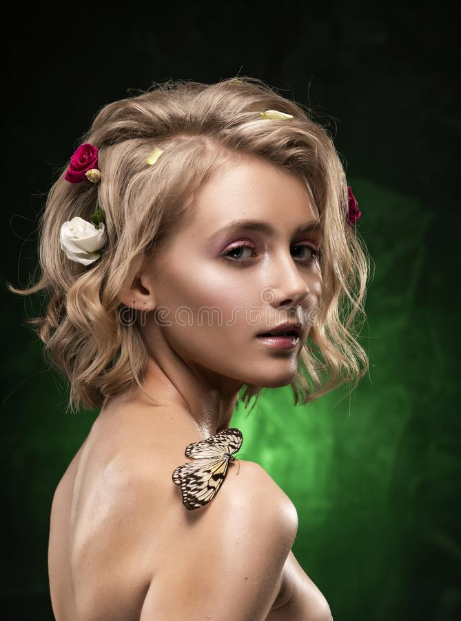 Bella giovane ragazza bionda sorridente con i fiori intrecciati nei suo capelli, corpo oleoso ed in una farfalla sulla sua spalla immagine stock libera da diritti