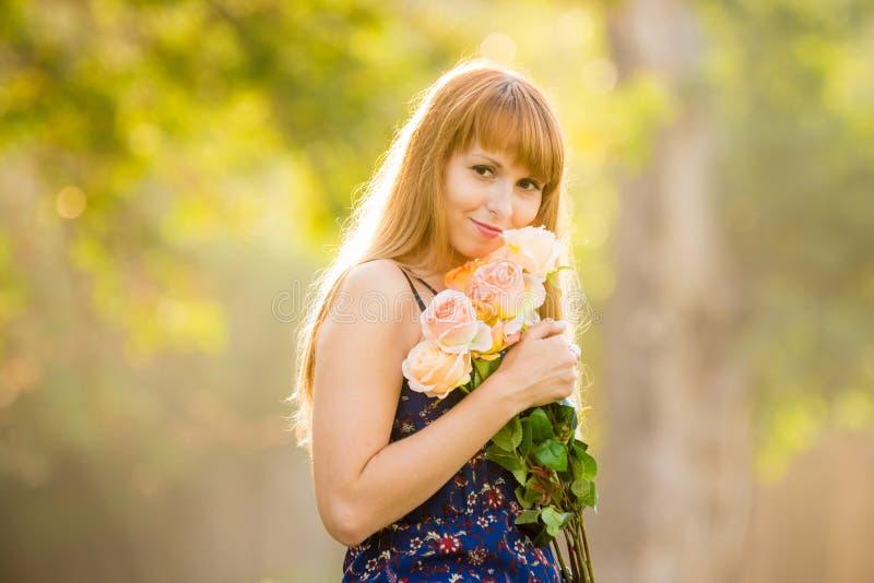 Bella giovane ragazza sexy che sta con il mazzo delle rose su un fondo di soleggiato verde vago immagine stock libera da diritti