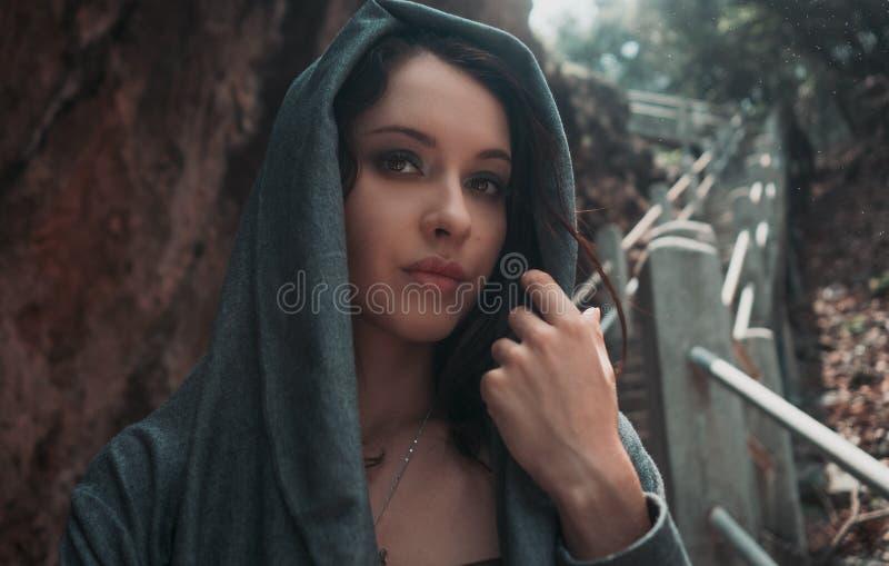 Bella giovane ragazza sexy con trucco luminoso in un cappuccio grigio immagini stock libere da diritti