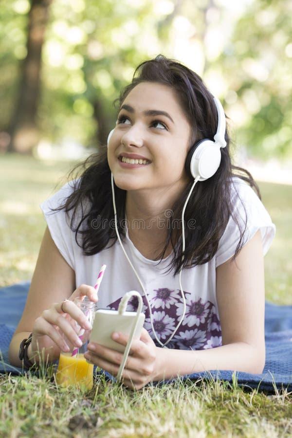 Bella giovane ragazza sorridente che si trova sull'erba, ascoltante in MU immagini stock
