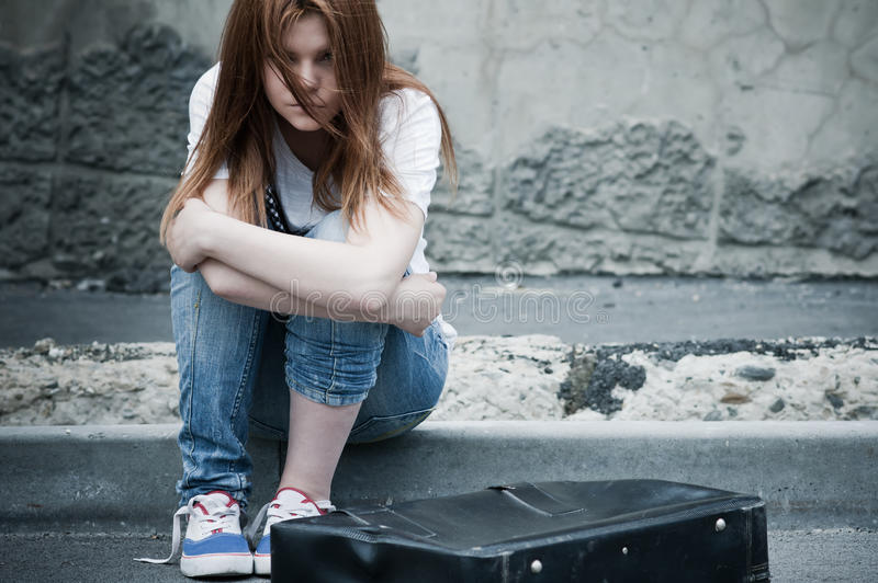 Bella giovane ragazza triste che si siede sull'asfalto immagine stock libera da diritti