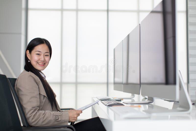 Bella giovane seduta asiatica nell'ufficio moderno felicemente, là a immagini stock