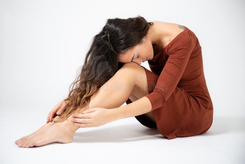 Bella giovane seduta castana dai capelli lunghi sul pavimento immagini stock libere da diritti