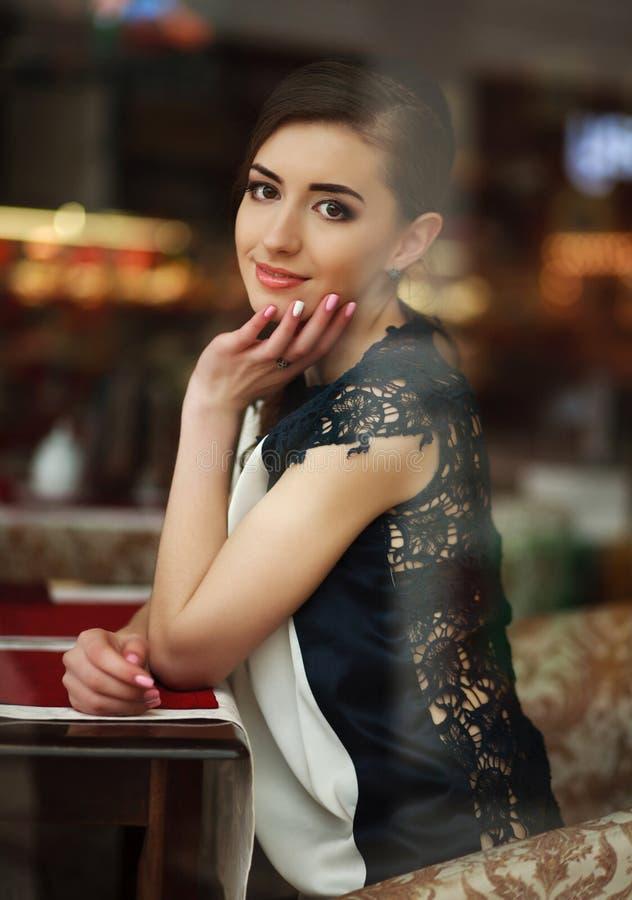 Bella giovane seduta castana della donna vaga vicino ad una finestra fotografie stock