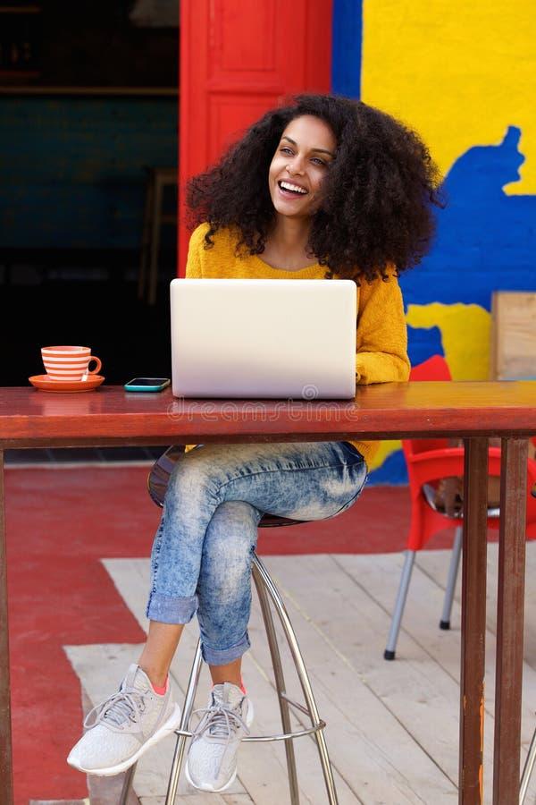 Bella giovane signora africana che si siede alla caffetteria con il computer portatile fotografia stock libera da diritti