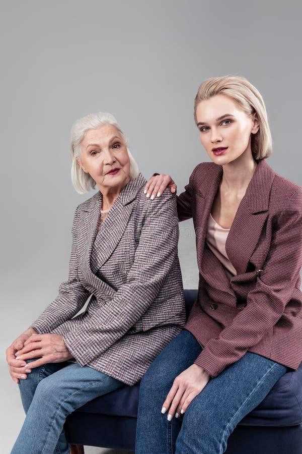 Bella giovane signora che si siede accanto a sua madre dai capelli corti fotografie stock