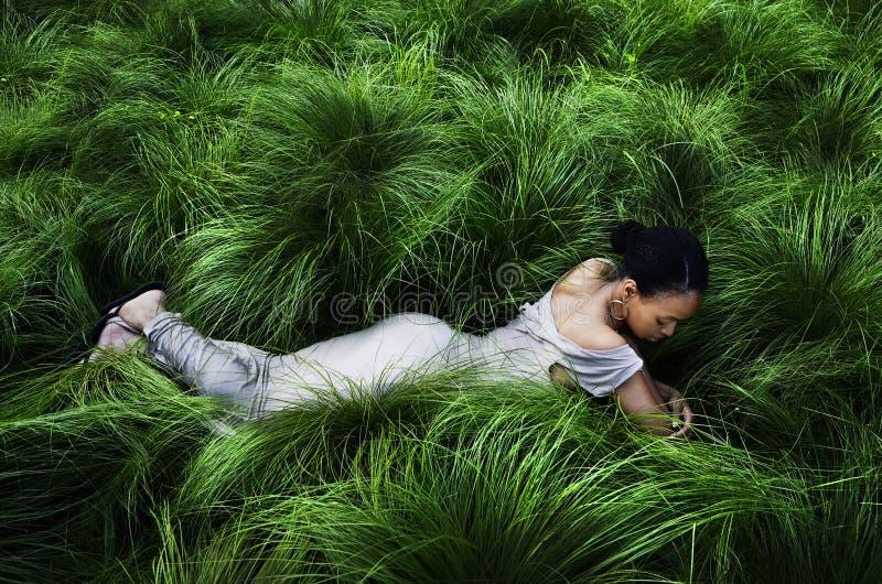 Bella giovane signora che si trova nell'alta erba fotografie stock