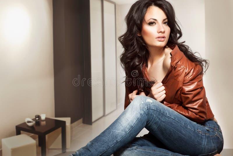 Bella giovane signora che sta in un interno alla moda immagini stock