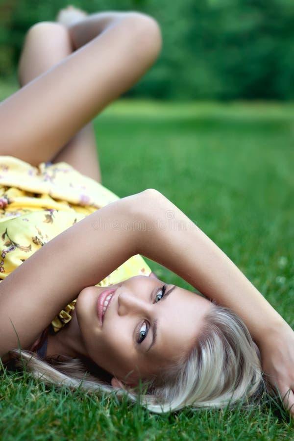 Bella giovane signora sorridente che mette sull'erba immagini stock libere da diritti