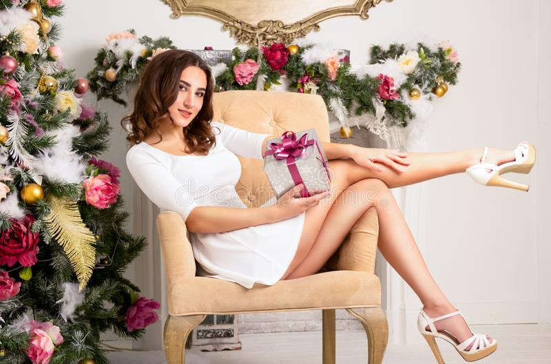 Bella giovane signora tenera in sedia vicino al contenitore di regalo della tenuta dell'albero di Natale fotografia stock