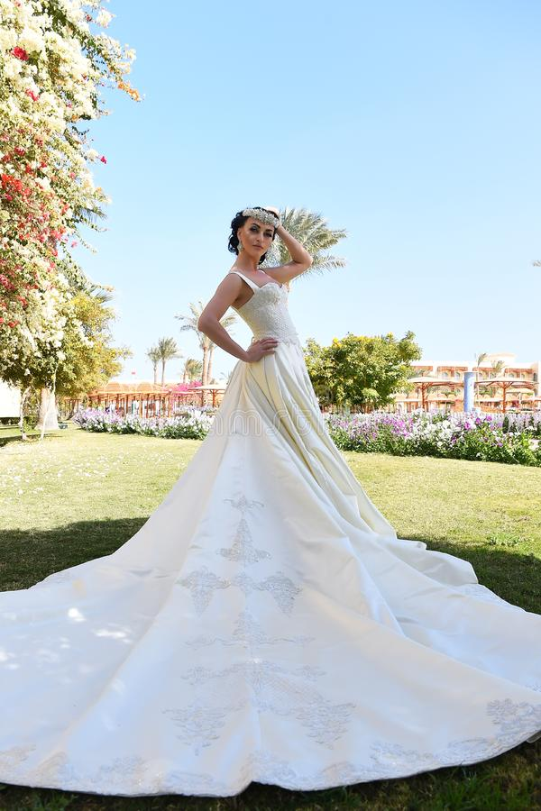 Bella giovane sposa castana sensuale in vestito da sposa bianco lungo fotografia stock