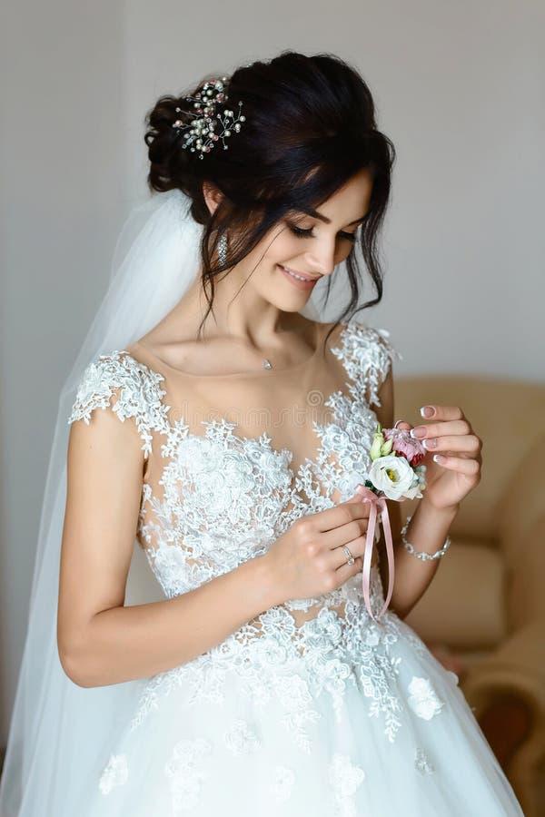 Bella giovane sposa caucasica esile che tiene un boutonniere del fiore Mattina della sposa fotografia stock libera da diritti