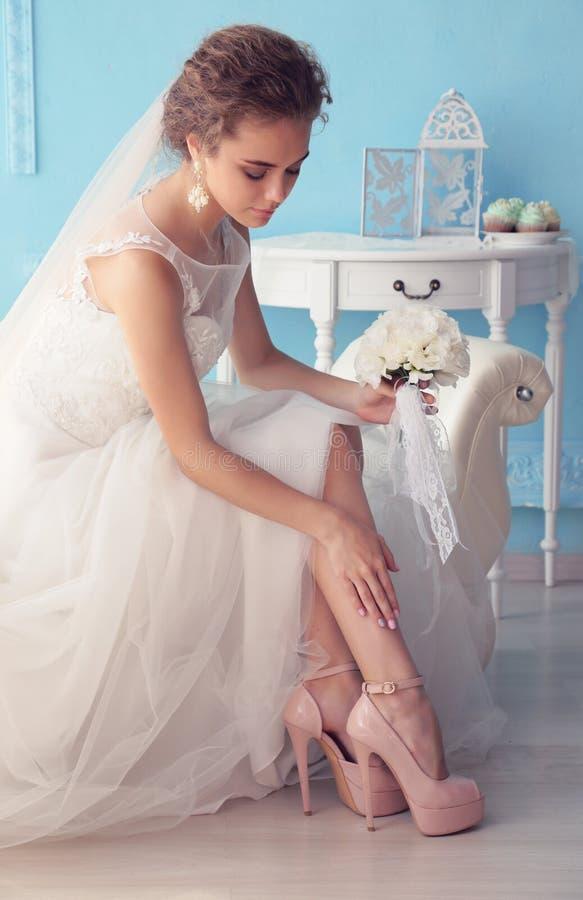 Bella giovane sposa con capelli ricci scuri in vestito da sposa lussuoso che posa alla stanza immagine stock libera da diritti