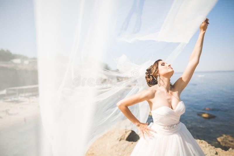 Bella giovane sposa con il mazzo nuziale che posa sul mare del fondo immagini stock libere da diritti
