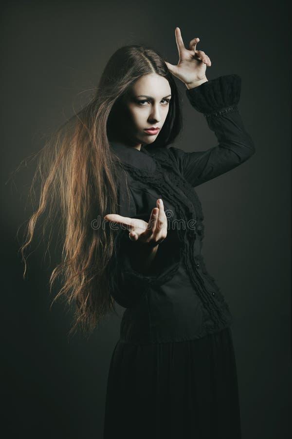 Bella giovane strega che lancia un incantesimo immagini stock