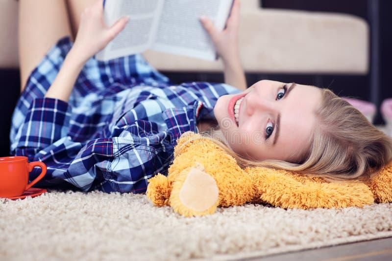 Bella giovane studentessa che legge un libro all'interno che si trova sul pavimento nel salone immagine stock