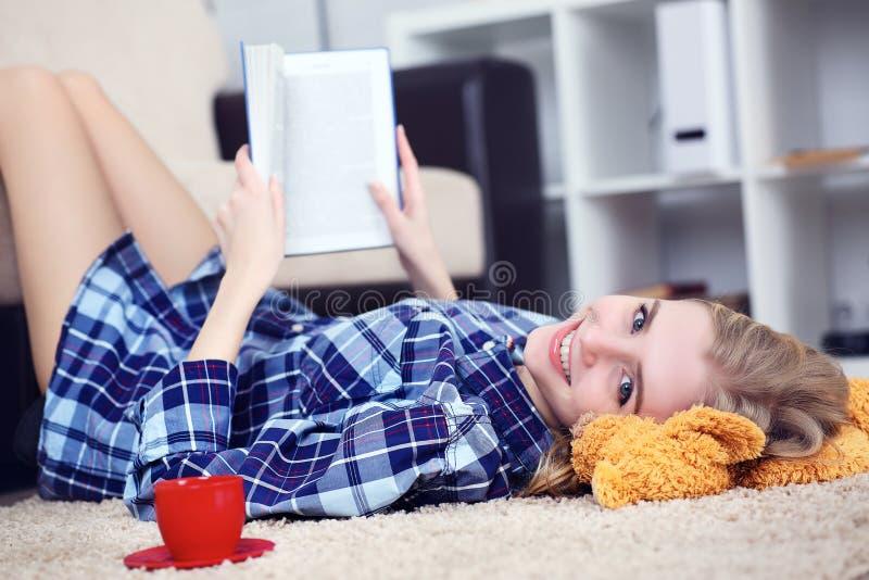 Bella giovane studentessa che legge un libro all'interno che si trova sul pavimento nel salone fotografia stock