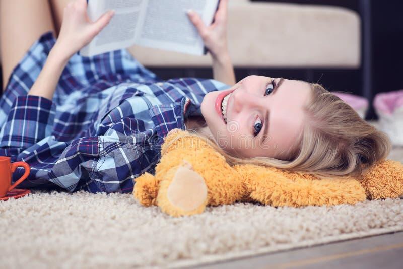 Bella giovane studentessa che legge un libro all'interno che si trova sul pavimento nel salone immagini stock