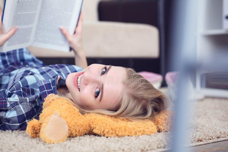 Bella giovane studentessa che legge un libro all'interno che si trova sul pavimento nel salone immagine stock libera da diritti