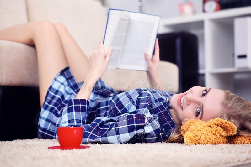 Bella giovane studentessa che legge un libro all'interno che si trova sul pavimento nel salone fotografie stock libere da diritti