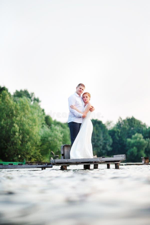 Bella giovani coppie, sposa e sposo di nozze posanti sul lago b fotografia stock