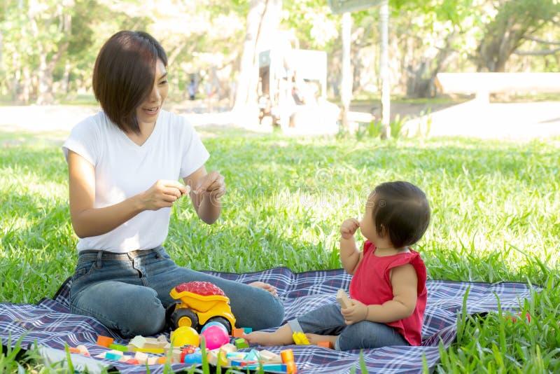 Bella giovani mamma e figlia asiatiche che giocano i blocchetti del giocattolo per l'apprendimento sviluppo felice e del divertim immagine stock