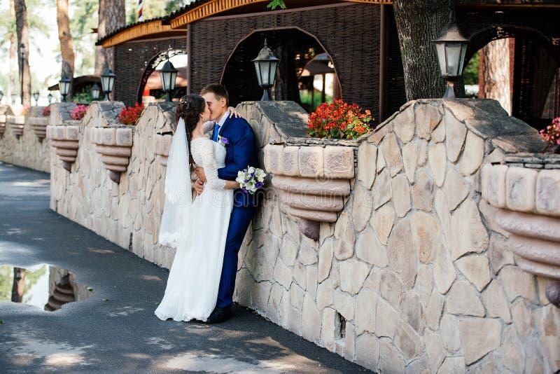 Bella giovani sposa e sposo che baciano vicino alla parete di pietra nel parco Coppie di nozze nell'amore al giorno del wedd fotografia stock