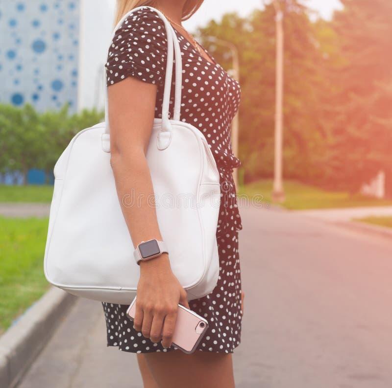 Bella grande borsa rossa alla moda sul braccio della ragazza in un vestito alla moda da estate, posante sulla via un nig caldo di immagine stock