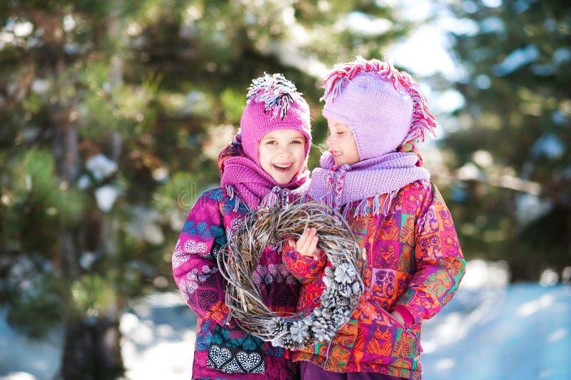 Bella immagine bianca di inverno in una foresta innevata in natura con i bambini Due gemelli delle sorelle in rivestimenti e capp immagini stock libere da diritti