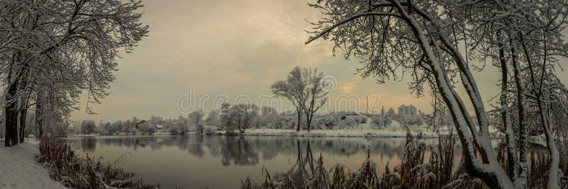 Bella immagine di inverno landscape vista panoramica dalla costa del fiume, laghi, stagno in un parco innevato della città attrav fotografie stock