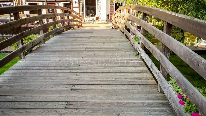 Bella immagine tonificata di piccolo ponte di legno attraverso il fiume in città europea al giorno soleggiato luminoso fotografie stock