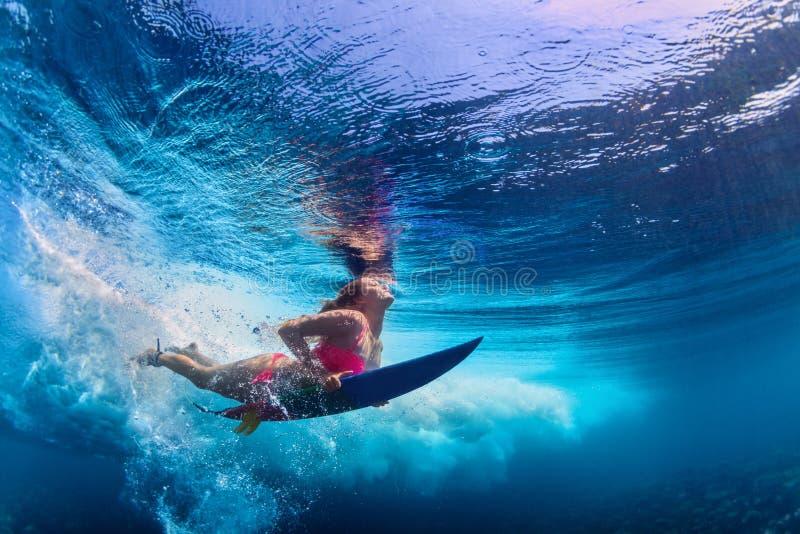 Bella immersione subacquea della ragazza del surfista sotto l'acqua con il bordo di spuma fotografie stock libere da diritti
