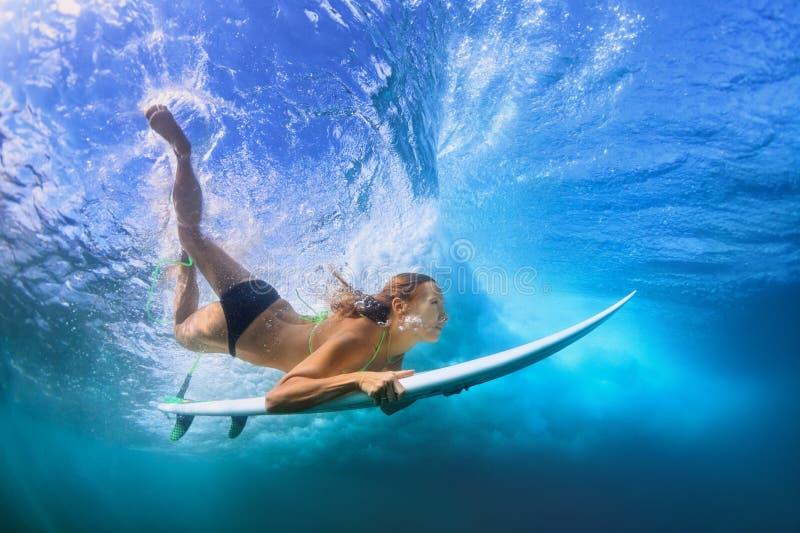 Bella immersione subacquea della ragazza del surfista sotto l'acqua con il bordo di spuma immagini stock libere da diritti