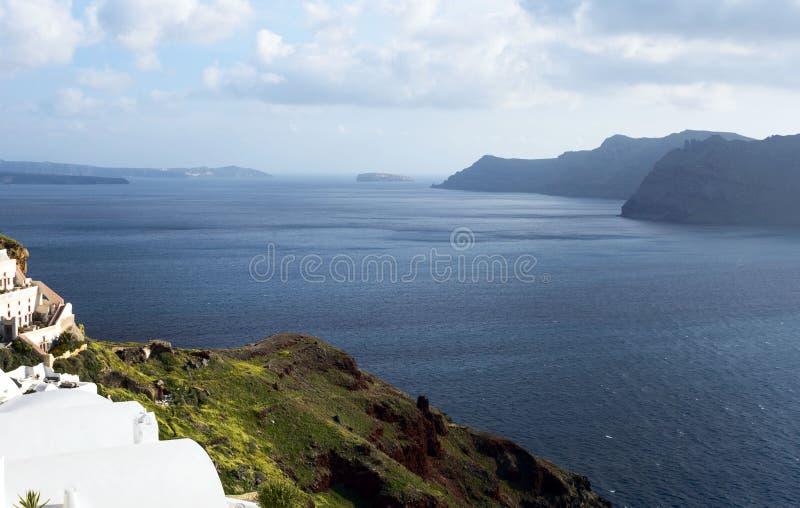 Bella isola di Santorini, Grecia Case greche bianche tradizionali contro il contesto del mare La città di OIA sul fotografia stock libera da diritti