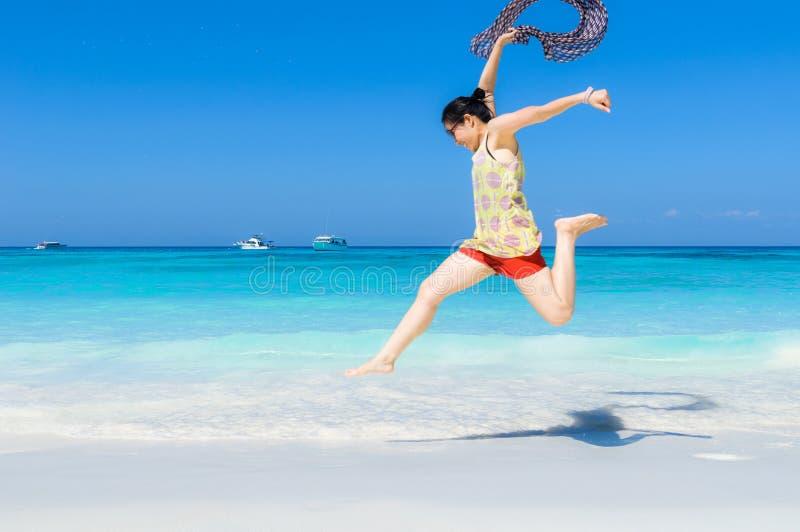 Bella la donna asiatica felice e allegra gode di di saltare su un briciolo fotografie stock