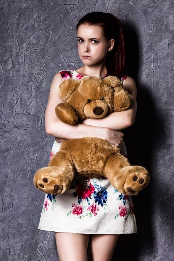 Bella la donna pensierosa o offensiva abbraccia un orsacchiotto riguarda un fondo grigio fotografia stock